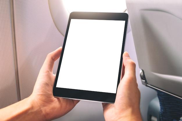 Mockup-afbeelding van een man die zwarte tablet-pc vasthoudt en bekijkt met een leeg wit bureaublad naast een vliegtuigvenster