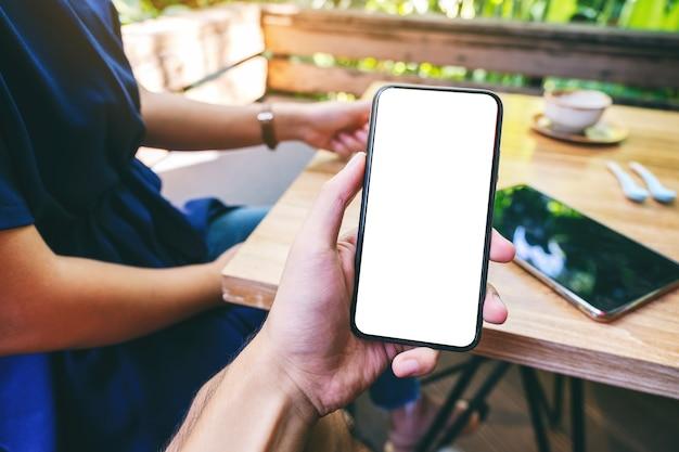 Mockup-afbeelding van een man met een zwarte mobiele telefoon met een leeg wit scherm met een vrouw die koffie drinkt in café