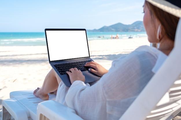 Mockup-afbeelding van een vrouw die een laptop gebruikt en typt met een leeg desktopscherm terwijl ze op een strandstoel op het strand ligt
