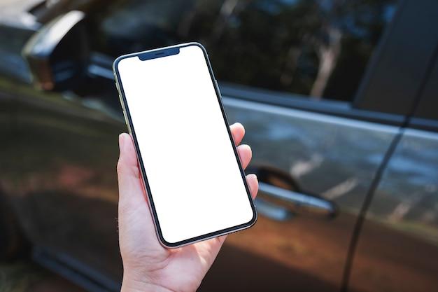 Mockup-afbeelding van een vrouw die een mobiele telefoon vasthoudt en gebruikt met een leeg scherm met een auto op de achtergrond