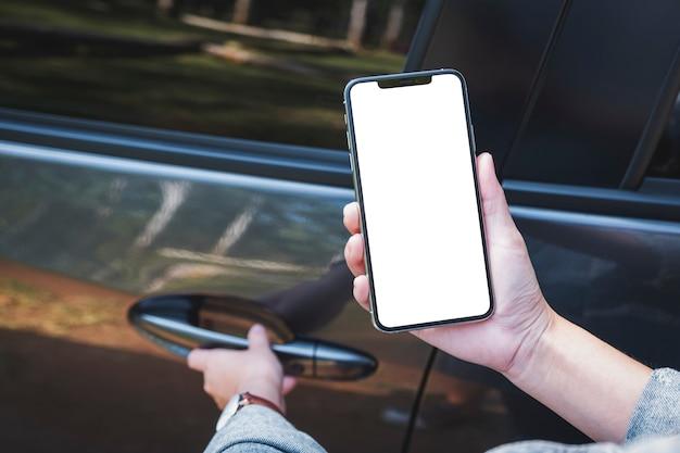 Mockup-afbeelding van een vrouw die een mobiele telefoon vasthoudt en gebruikt met een leeg scherm terwijl ze de autodeur opent