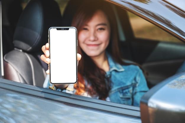 Mockup-afbeelding van een vrouw die een mobiele telefoon vasthoudt en toont met een leeg scherm terwijl ze in de auto zit