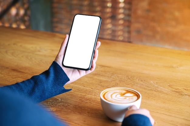 Mockup-afbeelding van een vrouw die een witte mobiele telefoon met een leeg scherm vasthoudt terwijl ze koffie drinkt op een houten tafel in café