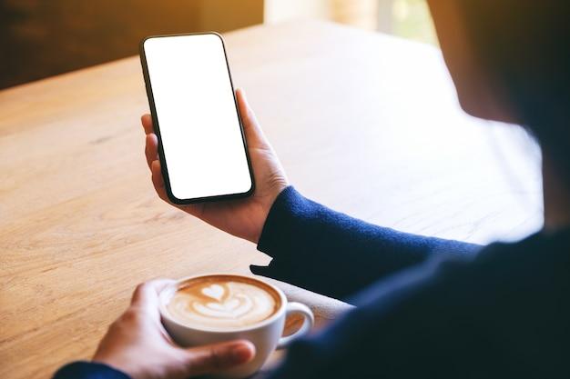 Mockup-afbeelding van een vrouw die een witte mobiele telefoon met een leeg scherm vasthoudt terwijl ze koffie drinkt