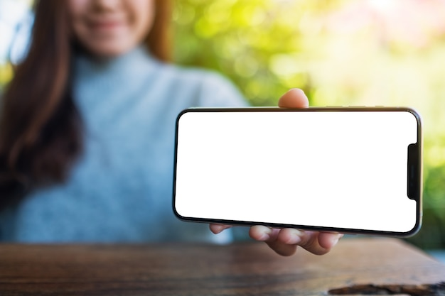 Mockup-afbeelding van een vrouw die een zwarte mobiele telefoon vasthoudt en toont met een leeg desktopscherm