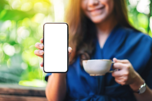 Mockup-afbeelding van een vrouw die een zwarte mobiele telefoon vasthoudt en toont met een leeg scherm met een groene natuurachtergrond