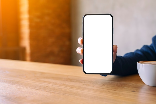 Mockup-afbeelding van een vrouw die een zwarte mobiele telefoon vasthoudt en toont met een leeg wit scherm terwijl ze koffie drinkt