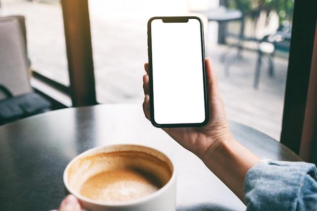Mockup-afbeelding van een vrouw die een zwarte mobiele telefoon vasthoudt met een leeg scherm terwijl ze koffie drinkt op tafel