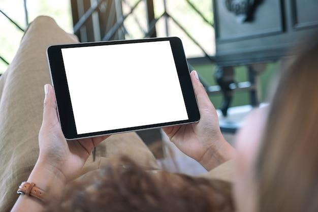 Mockup-afbeelding van een vrouw die een zwarte tablet-pc met een leeg wit bureaublad horizontaal houdt terwijl ze in de woonkamer ligt met een ontspannen gevoel