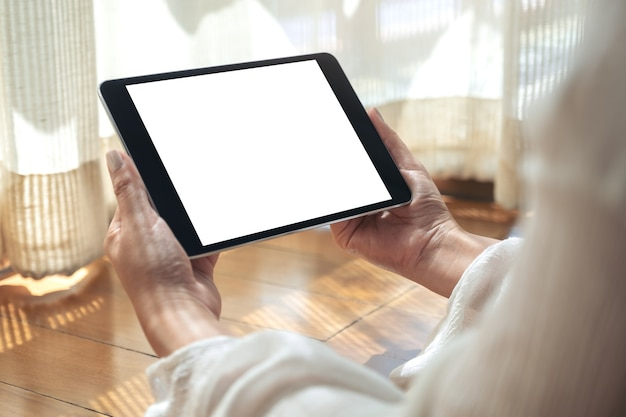 Mockup-afbeelding van een vrouw die een zwarte tablet-pc met een leeg wit bureaublad horizontaal houdt terwijl ze op de grond ligt met een ontspannen gevoel
