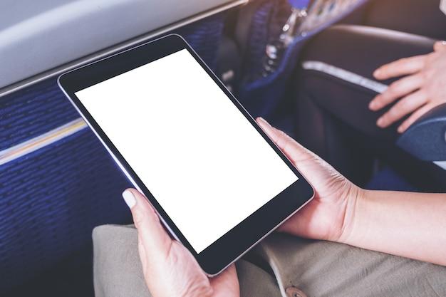 Mockup-afbeelding van een vrouw die een zwarte tablet-pc vasthoudt en bekijkt met een leeg wit bureaubladscherm terwijl ze in de cabine zit