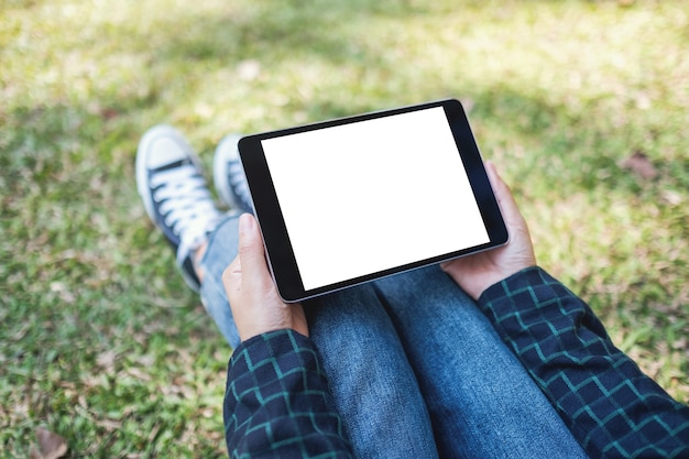 Mockup-afbeelding van een vrouw die een zwarte tablet-pc vasthoudt en gebruikt met een leeg wit bureaubladscherm terwijl ze buiten zit