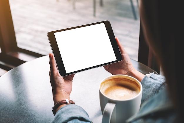 Mockup-afbeelding van een vrouw die een zwarte tablet vasthoudt met een wit leeg bureaubladscherm terwijl ze koffie drinkt