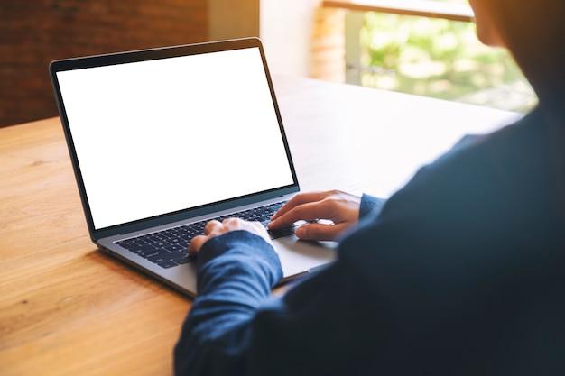 Mockup-afbeelding van een vrouw die gebruikt en typt op het toetsenbord van een laptopcomputer met een leeg wit desktopscherm op houten tafel