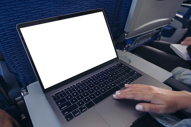 Mockup-afbeelding van een vrouw die het touchpad van de laptopcomputer met een leeg wit bureaubladscherm gebruikt en aanraakt terwijl ze in de cabine zit
