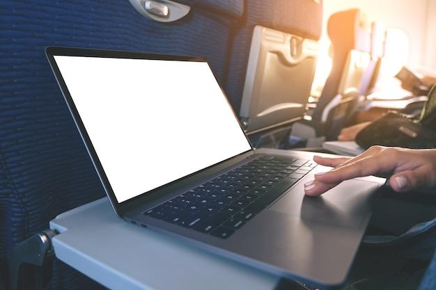 Mockup-afbeelding van een vrouw die het touchpad van een laptopcomputer gebruikt en aanraakt met een leeg wit bureaubladscherm terwijl ze in de cabine zit