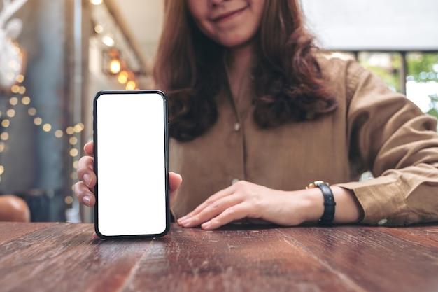 Mockup-afbeelding van een vrouw die houdt en zwarte mobiele telefoon met leeg wit scherm toont op de tafel in café