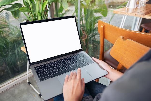 Mockup-afbeelding van een vrouw die laptop-touchpad gebruikt en aanraakt met een leeg wit bureaubladscherm terwijl ze in café zit