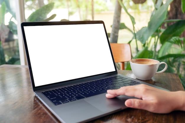 Mockup-afbeelding van een vrouw die laptop-touchpad gebruikt en aanraakt met een leeg wit bureaubladscherm terwijl ze koffie drinkt op houten tafel