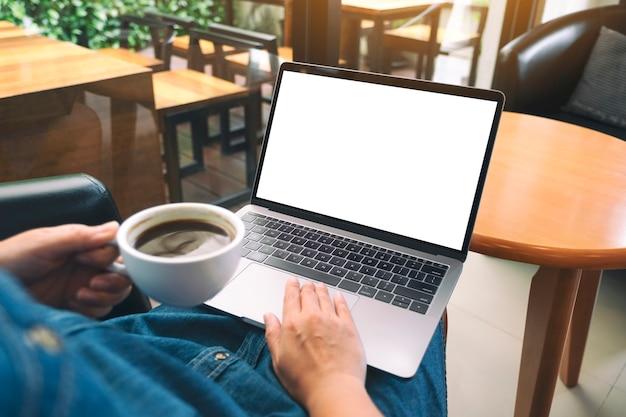 Mockup-afbeelding van een vrouw die laptop-touchpad gebruikt en aanraakt met een leeg wit bureaubladscherm terwijl ze koffie drinkt