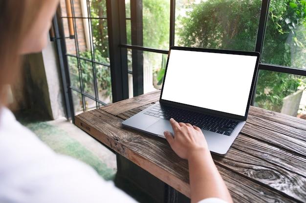 Mockup-afbeelding van een vrouw die laptop-touchpad gebruikt en aanraakt met een leeg wit bureaubladscherm