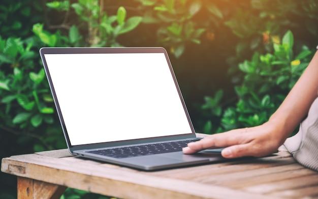 Mockup-afbeelding van een vrouw die laptop-touchpad gebruikt en aanraakt met een leeg wit desktopscherm op houten tafel