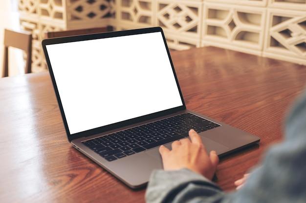 Mockup-afbeelding van een vrouw die laptop touchpad met leeg wit bureaublad op houten tafel gebruikt en aanraakt