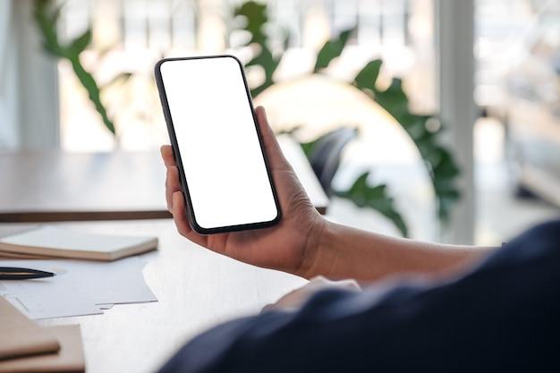 Mockup-afbeelding van een vrouw die mobiele telefoon met een leeg scherm vasthoudt en gebruikt tijdens het werken op kantoor
