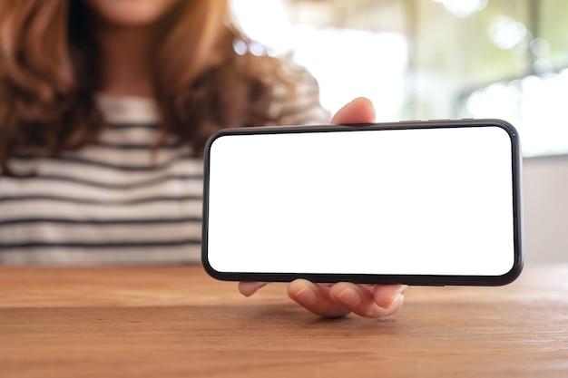 Mockup-afbeelding van een vrouw die witte mobiele telefoon met een leeg scherm horizontaal op houten tafel houdt