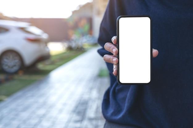 Mockup-afbeelding van een vrouw die zwarte mobiele telefoon met leeg zwart scherm in de buitenlucht houdt en toont