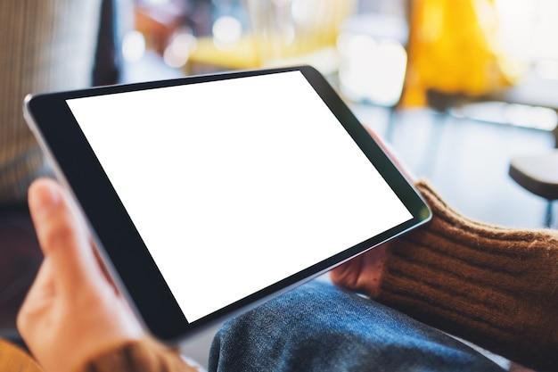 Mockup-afbeelding van een vrouw die zwarte tablet-pc zit en vasthoudt met een leeg wit bureaubladscherm