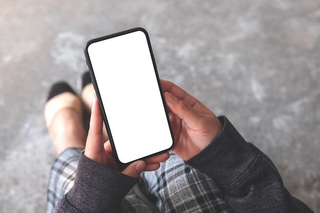 Mockup-afbeelding van een vrouw met een zwarte mobiele telefoon met een leeg bureaublad terwijl ze op de vloer zit