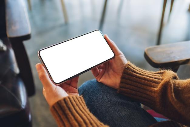 Mockup-afbeelding van een vrouw met een zwarte mobiele telefoon met een leeg bureaubladscherm