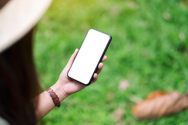 Mockup-afbeelding van een vrouw met een zwarte mobiele telefoon met een leeg desktopscherm in het park