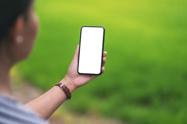 Mockup-afbeelding van een vrouw met een zwarte mobiele telefoon met een leeg desktopscherm met een wazige groene natuurachtergrond