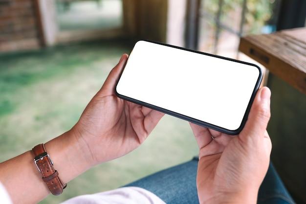 Mockup-afbeelding van een vrouw met een zwarte mobiele telefoon met een leeg desktopscherm terwijl ze in een café zit