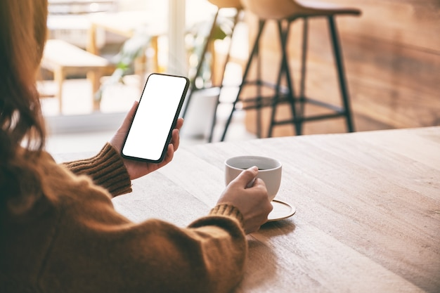 Mockup-afbeelding van een vrouw met een zwarte mobiele telefoon met een leeg scherm terwijl ze koffie drinkt