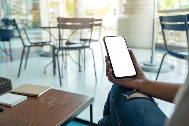 Mockup-afbeelding van een vrouw met een zwarte mobiele telefoon met een leeg wit bureaublad terwijl ze in café zit