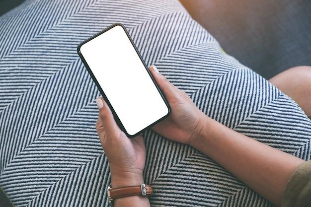 Mockup-afbeelding van een vrouw met een zwarte mobiele telefoon met een leeg wit bureaublad terwijl ze in de woonkamer zit met een ontspannen gevoel