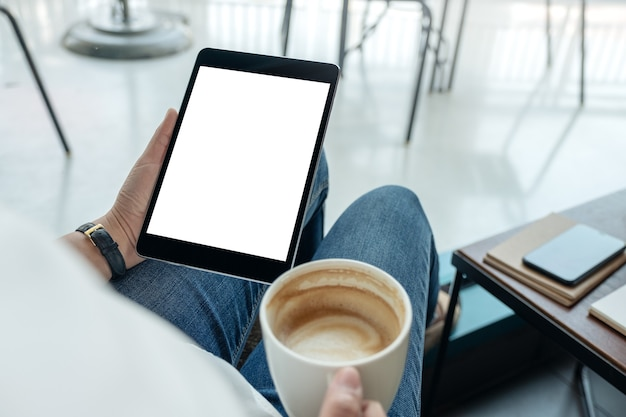 Mockup-afbeelding van een vrouw met een zwarte tablet-pc met een leeg scherm terwijl ze koffie drinkt in het café