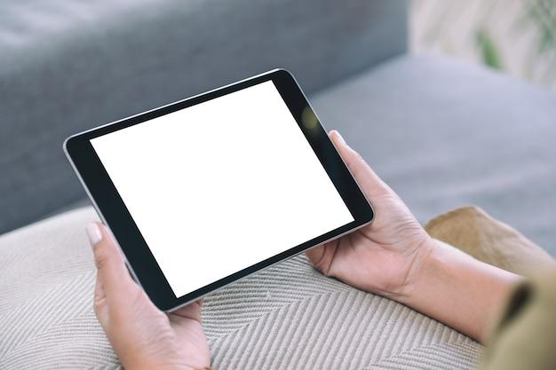 Mockup-afbeelding van een vrouw met een zwarte tablet-pc met een leeg wit bureaublad terwijl ze in de woonkamer zit met een ontspannen gevoel