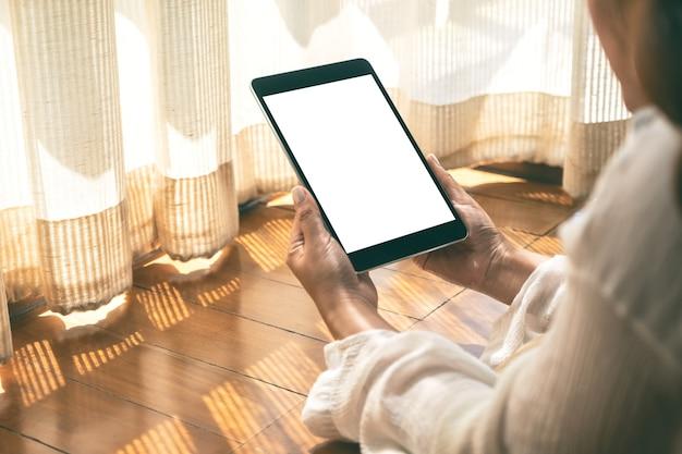 Mockup-afbeelding van een vrouw met een zwarte tablet-pc met een leeg wit bureaublad terwijl ze op de grond ligt met een ontspannen gevoel