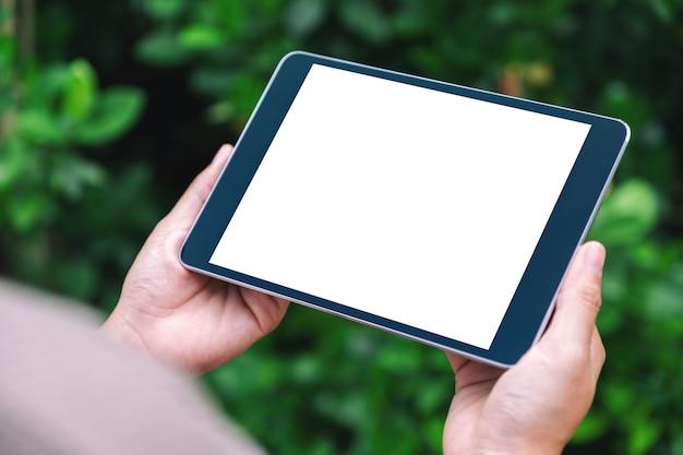 Mockup-afbeelding van een vrouw met een zwarte tablet-pc met een leeg wit desktopscherm in het park