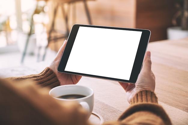 Mockup-afbeelding van een vrouw met een zwarte tablet-pc met een leeg wit scherm horizontaal met een koffiekopje op een houten tafel