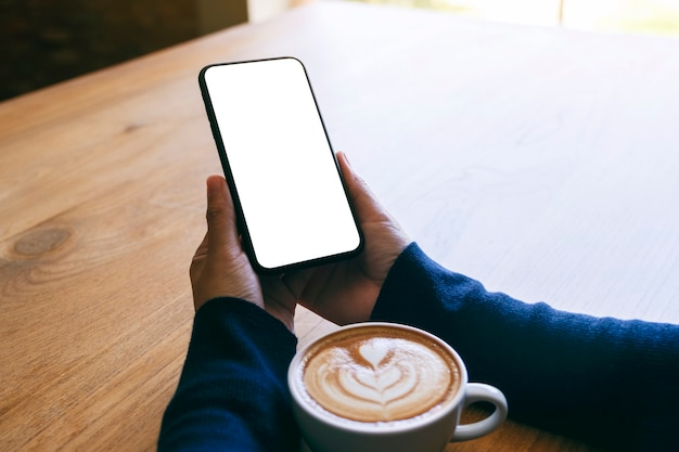 Mockup afbeelding van een vrouw met witte mobiele telefoon met leeg scherm met koffiekopje op houten tafel