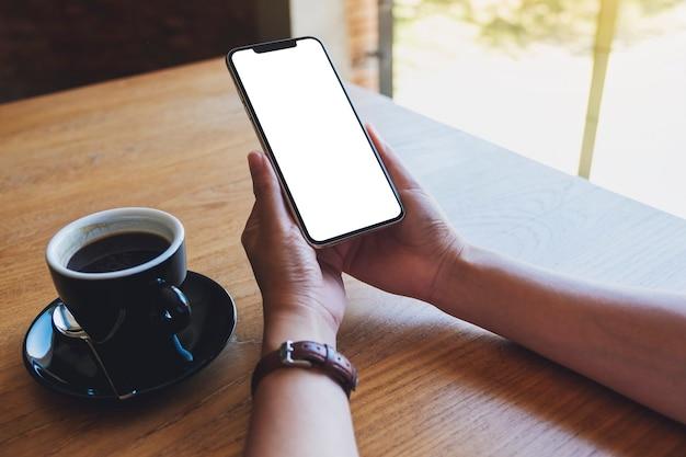 Mockup afbeelding van een vrouw met zwarte mobiele telefoon met leeg scherm met koffiekopje op houten tafel