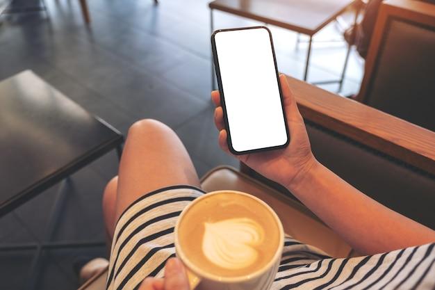 Mockup-afbeelding van een vrouw met zwarte mobiele telefoon met leeg scherm terwijl ze koffie drinkt in een modern café