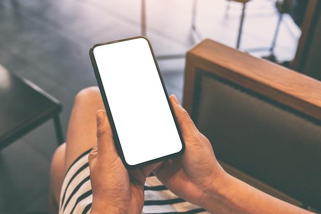 Mockup afbeelding van een vrouw met zwarte mobiele telefoon met leeg wit scherm in café