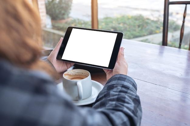 Mockup afbeelding van een vrouw met zwarte tablet pc met leeg scherm horizontaal met koffiekopje op houten tafel in café