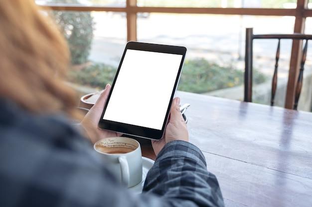 Mockup afbeelding van een vrouw met zwarte tablet pc met leeg scherm met koffiekopje op houten tafel in café